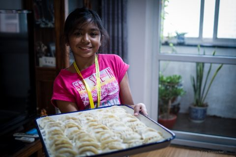 Young students showing off a plate of dumplings before cooking