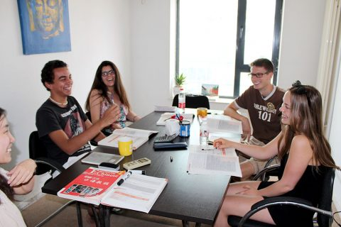 Four students sitting in a classroom laughing and learning