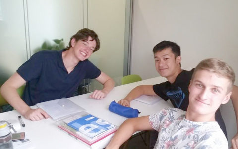 Three young male students in a classroom smiling at the camera
