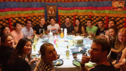 Ben and a large group of students and staff sitting around a table at Mongolian restaurant in Shanghai