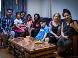Homestay family and students sitting at a living room table