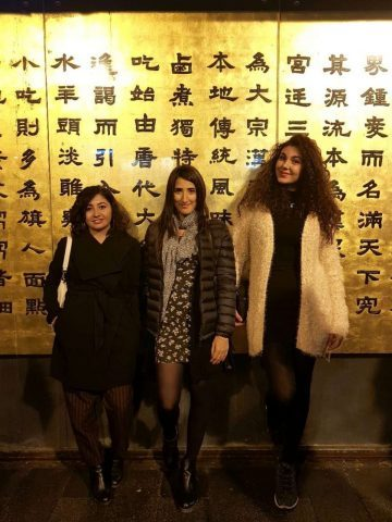 Enza with her friends in Beijing in front of a wall full of Chinese characters