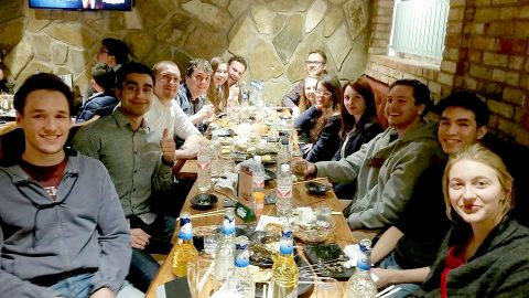 Large group of LTL staff and students sitting around a restaurant table