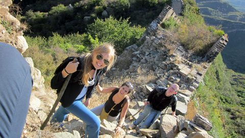 Three people hiking a wild section of the Great Wall