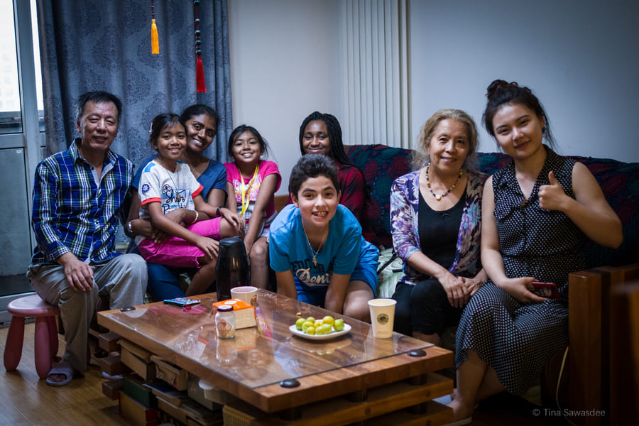 Students and homestay family sitting around a table in the living room