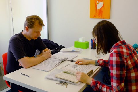 Student sitting at a desk in a classroom studying Chinese with a teacher present