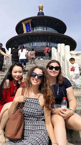 Three students sitting on the stairs leading up to the temple of heaven in Beijing